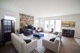 living room, stack stone, feature wall, large windows, wood floors